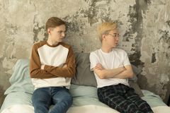 Giovane pensiero maschio gay pensieroso triste ai problemi di relazioni che si siedono sul letto con il ragazzo offensivo fotografie stock