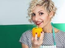 Giovane pepe sorridente della tenuta del cuoco della donna immagini stock