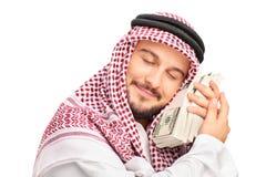 Giovane persona araba maschio che dorme sui soldi Immagine Stock
