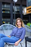 Giovane persona femminile che si siede nella sedia con il fondo della costruzione Fotografia Stock Libera da Diritti
