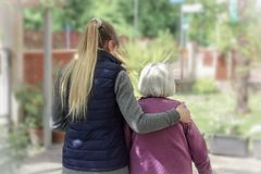 Giovane personale sanitario che cammina con la donna anziana nel giardino con fondo leggero immagini stock
