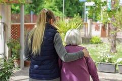 Giovane personale sanitario che cammina con la donna anziana nel giardino fotografia stock