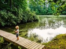 Giovane pesca del ragazzo da un ponte di legno fotografie stock