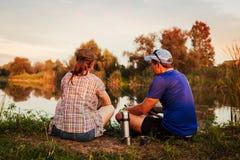 Giovane pesca delle coppie e tè bevente sul fiume al tramonto La gente che si rilassa e che raffredda all'aperto fotografia stock