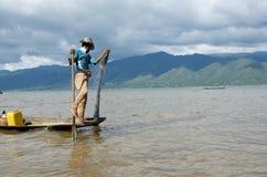 Giovane pescatore fuori per il pesce di mattina sul lago dell'intarsio Immagini Stock