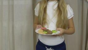 Giovane piatto bianco della tenuta della ragazza con i biscotti ed il giro del pan di zenzero intorno Ragazza in piatto rosso res archivi video