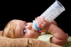 Giovane piccolo bambino che beve dalla sua bottiglia Fotografia Stock