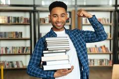 Giovane pila africana sicura della tenuta dello studente maschio di libri Immagine Stock Libera da Diritti