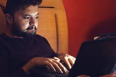Giovane pirata informatico che esamina computer portatile e che ottiene nella stanza scura fotografia stock libera da diritti