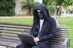 Giovane pirata informatico che lavora al suo computer portatile che si siede su un banco in un parco Immagini Stock Libere da Diritti
