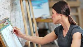 Giovane pittore femminile messo a fuoco incantante che lavora con il primo piano grigio di medium dell'immagine della pittura del stock footage