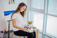 Giovane pittura della donna del pittore sul cavalletto in officina Immagine Stock Libera da Diritti