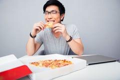 Giovane pizza mangiatrice di uomini asiatica Fotografia Stock