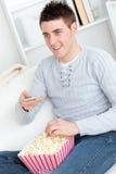 Giovane popcorn mangiatore di uomini Charming e TV di sorveglianza Fotografia Stock