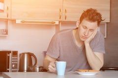 Giovane porridge mangiatore di uomini bello della farina d'avena nella cucina fotografie stock libere da diritti