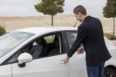 Giovane porta di apertura dell'uomo di affari dell'automobile bianca Fotografie Stock Libere da Diritti