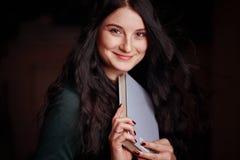 Giovane posa castana adorabile con un sorriso che tiene un libro in sue mani immagini stock