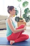 Giovane posa facente femminile fantastica del pesce di yoga sulla stuoia di yoga Immagine Stock