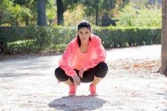 Giovane posa felice ed attraente della donna del corridore di sport rilassata al parco della città che guarda misura e sana dopo  fotografie stock