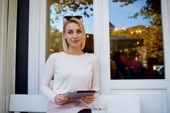 Giovane posa femminile attraente con la compressa digitale in mani mentre rilassandosi nella caffetteria comoda dopo la passeggia Fotografia Stock