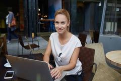 Giovane posa femminile incantante durante il lavoro sul suo NET-libro portatile, donna abbastanza caucasica che usando tecnologia Immagine Stock