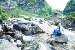 Giovane posa sorridente della donna felice al fiume sulla roccia, la gente della montagna di stile di vita sul concetto di vacanz fotografie stock libere da diritti