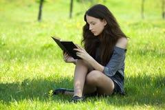 Giovane prato del libro di lettura dell'allievo Immagini Stock Libere da Diritti