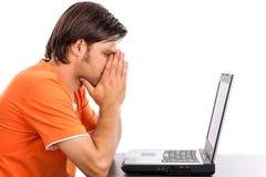 Giovane premuroso che esamina il suo computer portatile Fotografie Stock