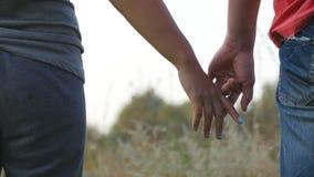 Giovane prender per manosi delle coppie all'aperto Uomo e donna che prendono armi sul fondo della natura Mani maschii e femminili Fotografia Stock