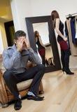 Giovane preoccupato che si siede sulla poltrona con la donna nel fondo che prova sui vestiti Immagini Stock Libere da Diritti