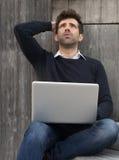 Giovane preoccupato o alleviato con il computer portatile Immagini Stock