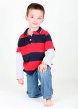 Giovane preschooler che si inginocchia sulla priorità bassa bianca Fotografia Stock