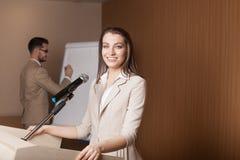 Giovane presentazione della tenuta dell'uomo d'affari e della donna di affari Immagini Stock Libere da Diritti