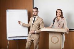 Giovane presentazione della tenuta dell'uomo d'affari e della donna di affari Immagini Stock