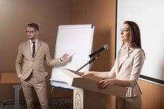 Giovane presentazione della tenuta dell'uomo d'affari e della donna di affari Fotografie Stock