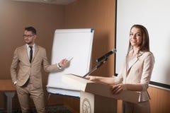 Giovane presentazione della tenuta dell'uomo d'affari e della donna di affari Fotografia Stock