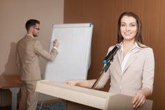 Giovane presentazione della tenuta dell'uomo d'affari e della donna di affari Immagine Stock