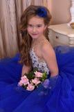 Giovane principessa in un vestito da sera blu con le rose e un piccolo cappello blu Immagini Stock