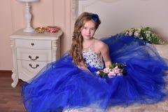Giovane principessa in un vestito da sera blu con le rose e un piccolo cappello blu Immagine Stock