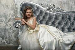Giovane principessa vittoriana che si siede su un sofà d'argento immagini stock