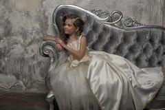 Giovane principessa vittoriana che si siede su un sofà d'argento fotografia stock libera da diritti