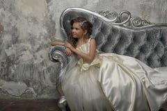 Giovane principessa vittoriana che si siede su un sofà d'argento fotografie stock libere da diritti