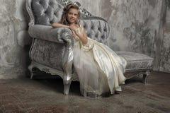 Giovane principessa vittoriana che si siede su un sofà d'argento immagine stock libera da diritti
