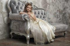 Giovane principessa vittoriana che si siede su un sofà d'argento immagine stock