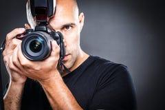 Giovane, pro fotografo maschio nel suo studio durante il tiro di foto immagine stock