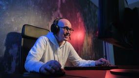Giovane pro gamer che gioca in video gioco online, colloqui con i giocatori di gruppo tramite il microfono Stanza colorata neon e video d archivio