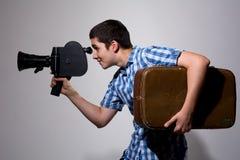 Giovane produttore cinematografico gay con la vecchia cinepresa e una valigia nel suo immagine stock libera da diritti