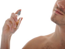 Giovane profumo maschio dello spruzzo del colpo a macroistruzione sulla sua pelle Immagini Stock Libere da Diritti