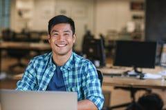 Giovane progettista asiatico sorridente che per mezzo di un computer portatile al suo scrittorio fotografia stock libera da diritti
