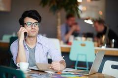 Giovane progettista creativo Speaking dal telefono in caffè Fotografia Stock